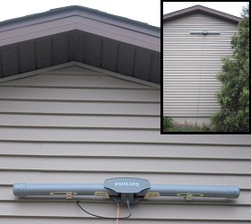 photo of Philips MANT950 amplified TV antenna mounted on side of house, under eave of roof (inset photo shows wider view, including copper grounding wire)